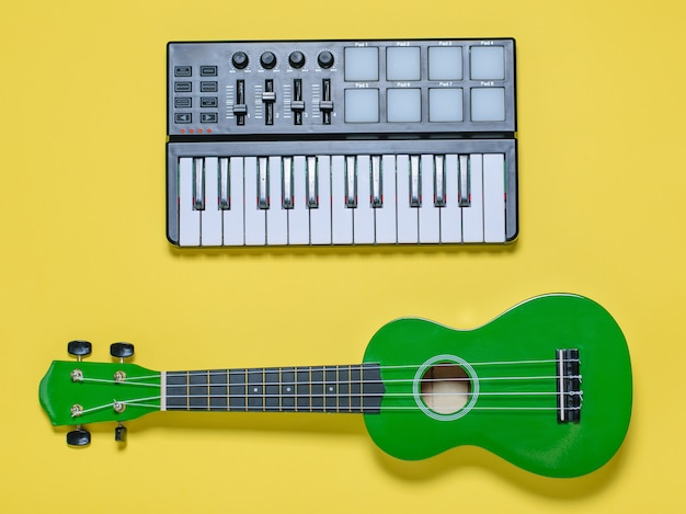 Green ukulele and music mixer on yellow background. the view from the top.