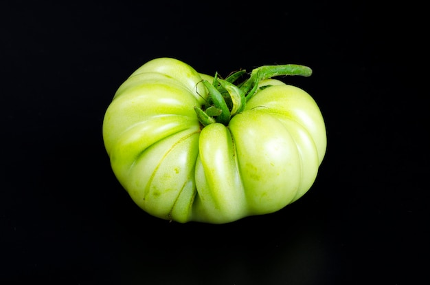 Green unripe tomato on black background. photo