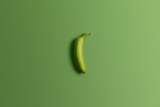Green unripe whole banana on bright studio background. tasty appetizing tropical fruit. clean eating, healthy nutritious and dietary snack. top view and flat lay. horizontal shot. food concept