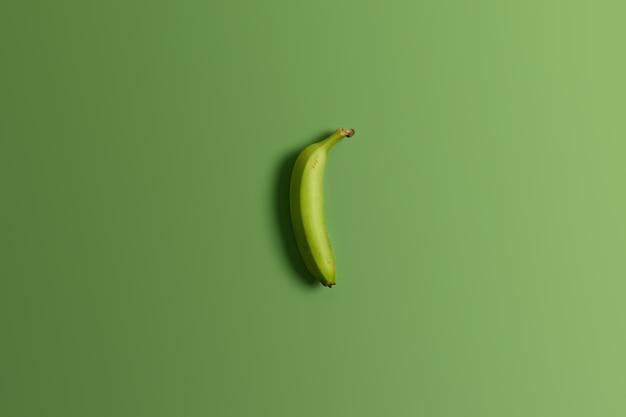 밝은 스튜디오 배경에 녹색 설 익은 전체 바나나. 맛있는 식욕을 돋우는 열대 과일. 깨끗한 식사, 건강에 좋은 영양 및식이 간식. 평면도 및 평면 배치. 수평 샷. 음식 개념