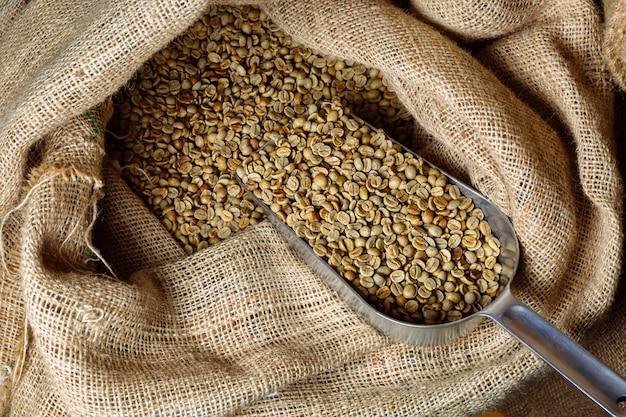 緑の未焙煎コーヒーは黄麻布の袋にあり、袋には穀物を振りかけるためのスクープがあります