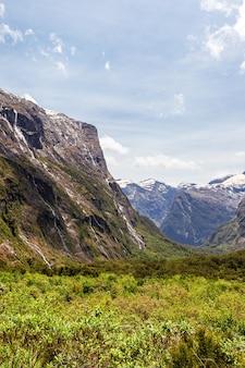 Зеленая долина и отвесные скалы на пути к южному острову фьордленд, новая зеландия
