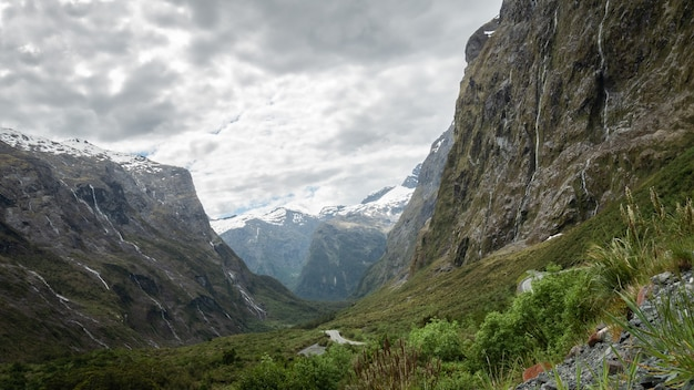 Зеленая долина, полная водопадов и заснеженных гор на заднем плане, снята в пасмурный день новая зеландия