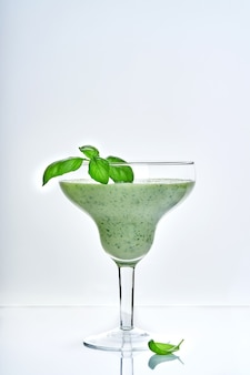 Green vegetable juice or smoothie garnished with leaf of fresh basil in coctail margarita glass isolated on white.