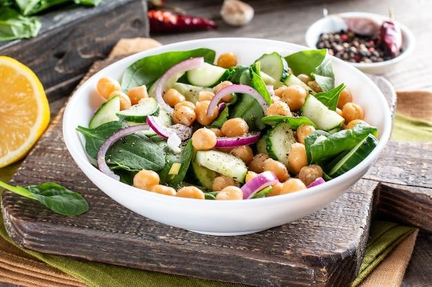 Салат из зеленых овощей с нутом, шпинатом, огурцом, красным луком и зеленью на деревянном столе