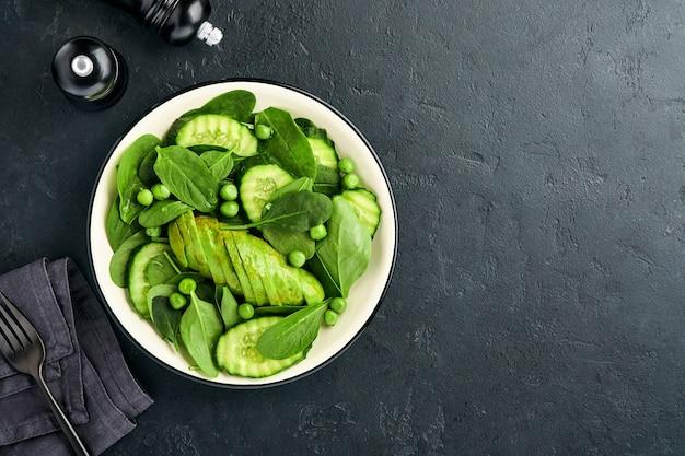 Салат из зеленых овощей со шпинатом, авокадо, зеленым горошком и оливковым маслом в миске на фоне темного сланца, камня или бетона. вид сверху с копией пространства. зеленые овощи для концепции диеты.