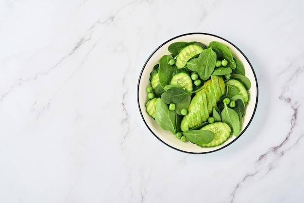 Салат из зеленых овощей со шпинатом, авокадо, зеленым горошком и оливковым маслом в миске на светло-сером фоне из шифера, камня или бетона. вид сверху с копией пространства. зеленые овощи для концепции диеты.