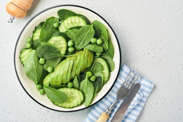 Салат из зеленых овощей со шпинатом, авокадо, зеленым горошком и оливковым маслом в миске на светло-сером сланце