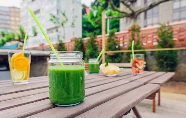 屋外の木製テーブルの上に緑の野菜のスムージーと注入されたフルーツウォーターカクテル。健康的なオーガニックサマードリンクのコンセプトです。