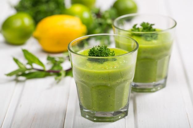 Зеленые овощные коктейли в очках на деревянном столе