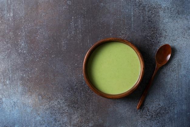 Green vegetable soup on black grey minimalism, top view