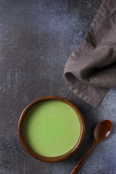 Green vegetable soup on black grey minimalism, vertical top view