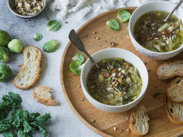 Green vegetable vegan soup from keil, brussels sprouts, zucchini, leek with various germinated seeds and sprouts