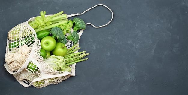 Зеленые овощи и фрукты в многоразовом пакете на темном бетонном фоне