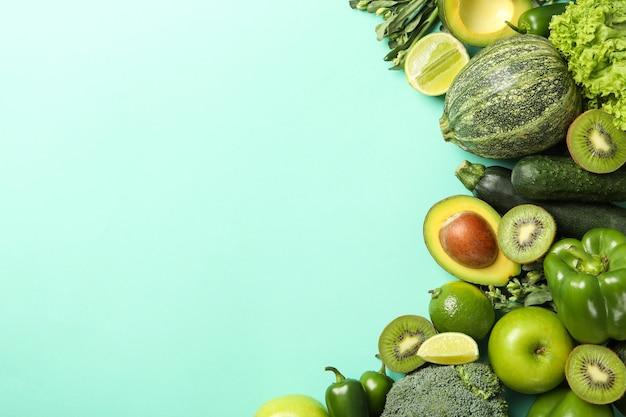 Зеленые овощи и фрукты на фоне мяты