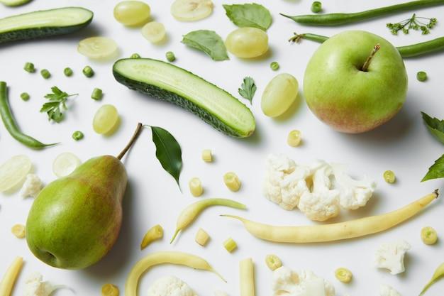 白いテーブルのための緑の野菜や果物。ビーガンのための健康的な食事と食べ物