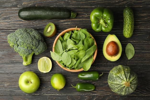 緑の野菜と果物の木製の背景