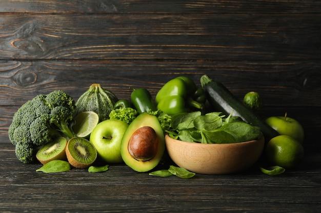 Зеленые овощи и фрукты на деревянных фоне