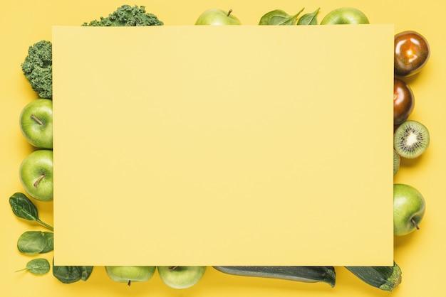 黄色の背景に緑の野菜や果物。りんご、梨、ケールサラダ、ほうれん草、キウイ、グリーントマト、ズッキーニ