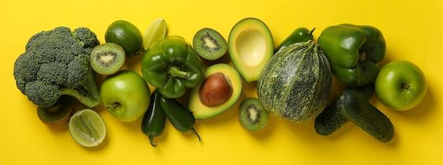 Зеленые овощи и фрукты на желтой поверхности