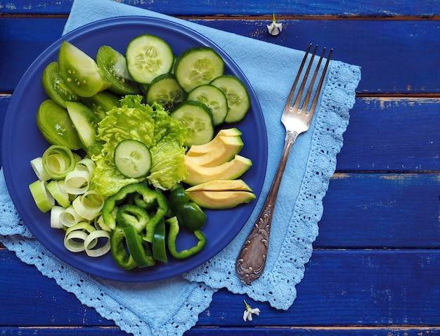 緑の野菜と果物-青い木の表面にサラダレタス、キュウリ、ニラ、アボカド、リンゴ、ピーマン