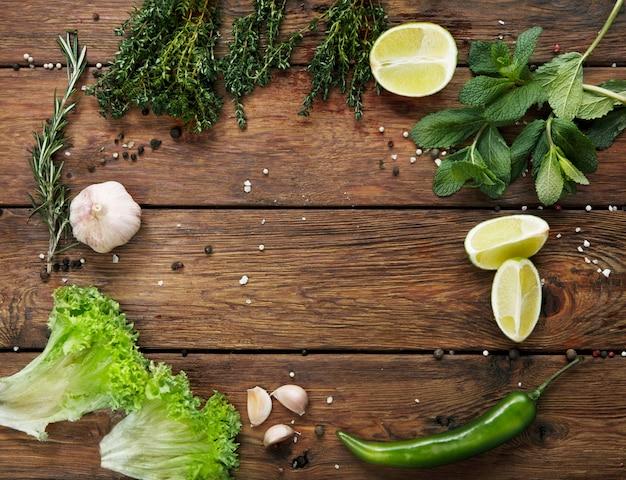 Зеленые овощи и фрукты с деревенским деревянным столом копией пространства