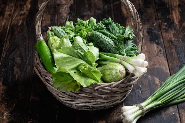 暗い木製の背景に緑の野菜とハーブ