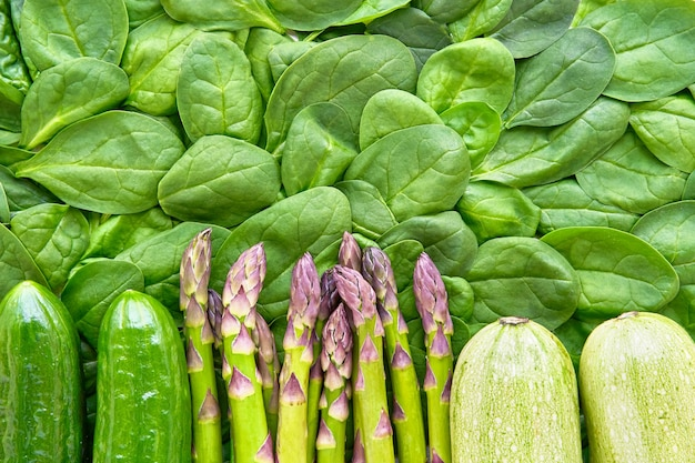 緑の野菜の背景アスパラガスほうれん草きゅうりとズッキーニの健康食品のフラットレイと