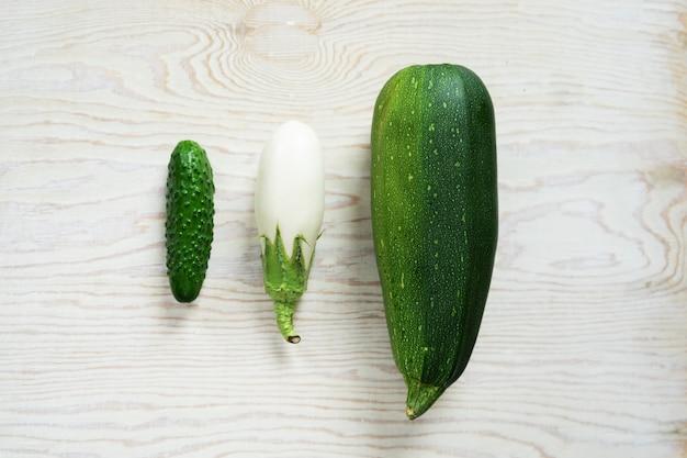 明るい背景に緑の野菜、キャベツ、キュウリ、ディル、白ナス。