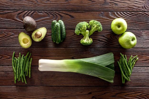 Зеленые овощи, огурец, авокадо, брокколи, бобы, лук-порей и свежее яблоко на темном деревянном фоне
