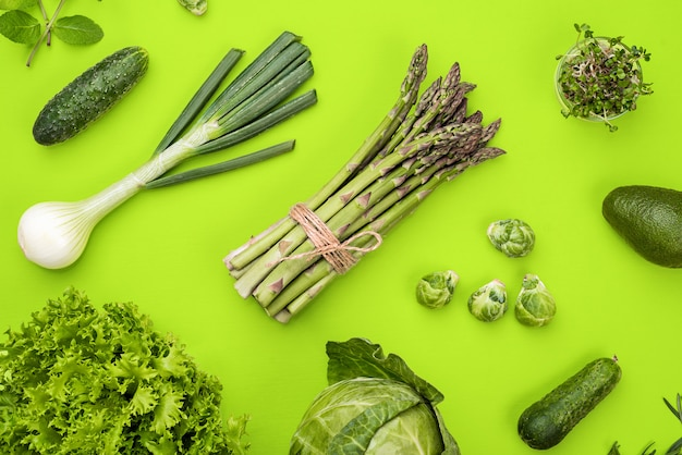 Green vegetables flat lay concept on green background