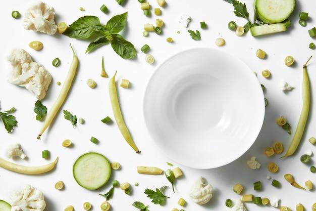 緑の野菜、果物、白いテーブルの上のプレート。ビーガンのための健康的な食事と食べ物