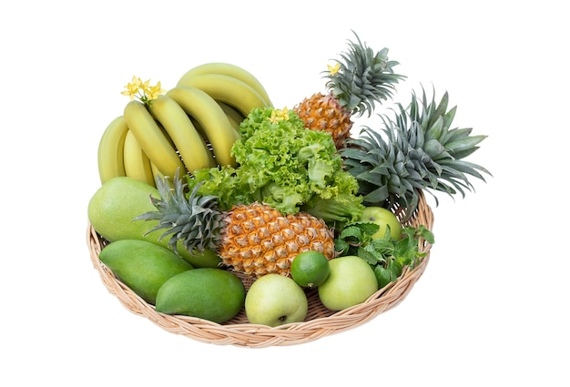 Green vegetables and fruits in the basket isolated on the white background.