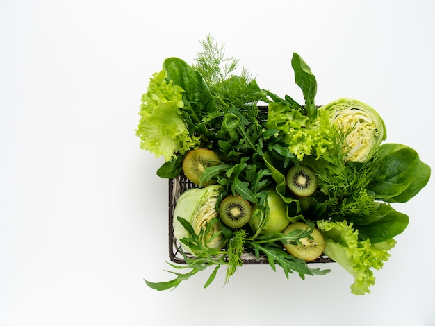 Green vegetables and fruits in basket.