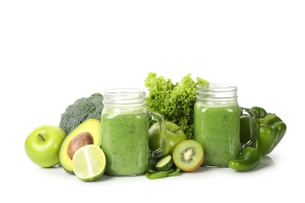 Green vegetables, fruits and jar of smoothie isolated on white background