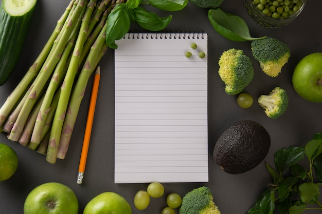Green vegetables on gray background with notebook for notes.