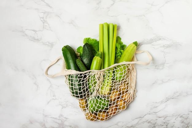 大理石の背景にストリングバッグの緑の野菜。