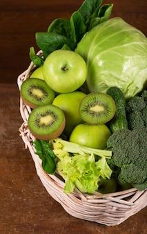 녹색 채소-키위, 양배추, 허브, 셀러리, 브로콜리, 오이 바구니에 나무 테이블