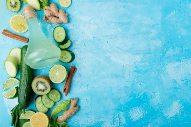 Green vegetables and lemon juice on blue
