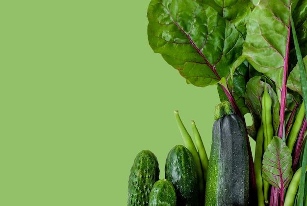 キュウリ、ズッキーニ、分離された緑の背景の葉のような緑の野菜。コピースペース