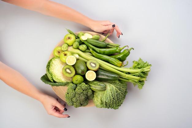 白い背景の上の木製プレートに緑の野菜