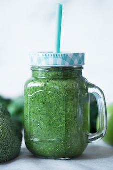 Green vegetables smoothies prepared with cauliflower on a white