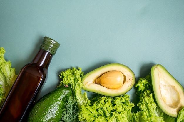 緑の背景に油のガラスの束と緑の野菜アボカドロマーノサラダグリーン上面図プラスチックなし健康的な食事の概念