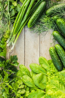 Green vegetables on a wooden background.
