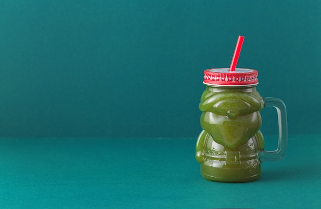 Green vegetal smoothie on blue background with copy space in glass santa claus jar. healthy eating, zero waste concept