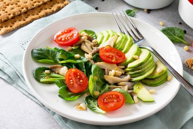 아보카도 버섯 그릇에 녹색 채식 아침 식사 체리 토마토 소나무 견과류 시금치와 비네 그레트 소스 드레싱 채식 음식 다이어트 개념