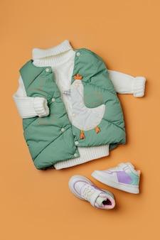 주황색 배경에 따뜻한 스웨터가 있는 녹색 조끼 재킷. 스타일리시한 아동복. 겨울 패션 복장