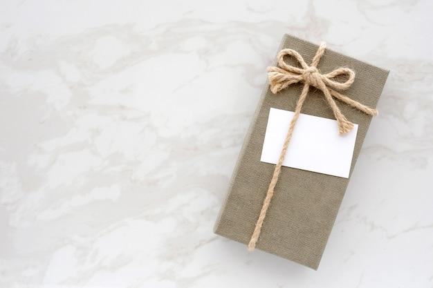 白い大理石の背景にグリーンヴィンテージギフトボックスの白と白の空白のカード