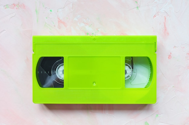 Green vintage vhs video tape on pink surface