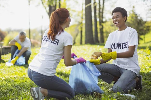 Зеленое волонтерство. оптимистичные два добровольца держат мешок для мусора и общаются